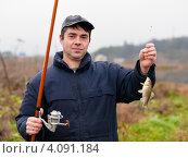 Купить «Мужчина с пойманной рыбой и удочкой в руках», эксклюзивное фото № 4091184, снято 5 ноября 2012 г. (c) Игорь Низов / Фотобанк Лори