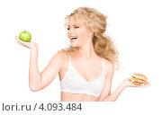 Купить «Привлекательная девушка с волнистыми волосами с зеленым яблоком и гамбургером в руке», фото № 4093484, снято 21 ноября 2009 г. (c) Syda Productions / Фотобанк Лори