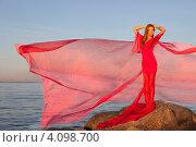 Молодая девушка в развевающемся красном платье стоит на берегу. Стоковое фото, фотограф Литвяк Игорь / Фотобанк Лори