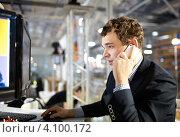 Купить «Молодой человек работает на компьютере и разговаривает по телефону», фото № 4100172, снято 3 ноября 2012 г. (c) Данил Руденко / Фотобанк Лори