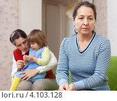 Купить «Конфликт поколений. Обиженная пожилая женщина сидит на фоне дочери и внучки», фото № 4103128, снято 1 декабря 2012 г. (c) Яков Филимонов / Фотобанк Лори