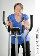 Купить «Пожилая женщина на  занимается фитнесом на тренажере», фото № 4108396, снято 20 ноября 2012 г. (c) Tatjana Baibakova / Фотобанк Лори