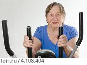 Купить «Пожилая женщина занимается на тренажере», фото № 4108404, снято 20 ноября 2012 г. (c) Tatjana Baibakova / Фотобанк Лори