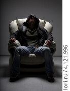 Опасный молодой человек сидит в кресле. Стоковое фото, фотограф Syda Productions / Фотобанк Лори