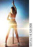 Купить «Молодая девушка в короткой юбке возле шеста», фото № 4129908, снято 5 февраля 2012 г. (c) chaoss / Фотобанк Лори