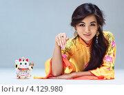 Купить «Симпатичная азиатская девушка в жёлтом халате на сером фоне», фото № 4129980, снято 5 декабря 2011 г. (c) chaoss / Фотобанк Лори