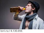 Модный мужчина в шляпе пьет текилу из бутылки, серый фон. Стоковое фото, фотограф Logunov Maxim / Фотобанк Лори