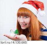 Симпатичная рыжеволосая девушка в шапочке Санта Клауса с новогодними игрушками на ладони. Стоковое фото, фотограф Logunov Maxim / Фотобанк Лори