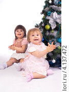Две нарядные маленькие девочки у новогодней елки, изолировано на белом фоне. Стоковое фото, фотограф Евгений Андреев / Фотобанк Лори
