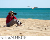 Купить «Девушка на песчаном пляже фотографирует летящую чайку, море на заднем плане», фото № 4140216, снято 1 сентября 2012 г. (c) SummeRain / Фотобанк Лори