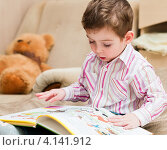 Купить «Маленький мальчик рассматривает картинки в книжке», эксклюзивное фото № 4141912, снято 13 ноября 2012 г. (c) Игорь Низов / Фотобанк Лори