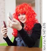 Купить «Веселая девушка в красном карнавальном парике смотрится в зеркало», фото № 4147676, снято 21 декабря 2012 г. (c) Яков Филимонов / Фотобанк Лори
