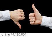 Две руки показывают жесты: большой палец  вверх и вниз. Стоковое фото, фотограф pzAxe / Фотобанк Лори