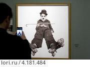 """Купить «Человек снимает фотографию """"Каток"""" на телефон на выставке """"Чарли Чаплин"""" в Мультимедиа Арт Музее города Москвы», эксклюзивное фото № 4181484, снято 8 января 2013 г. (c) Николай Винокуров / Фотобанк Лори"""
