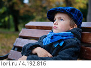 Портрет задумчивого мальчика в осенней одежде на скамейке в парке. Стоковое фото, фотограф Римма Зайцева / Фотобанк Лори