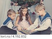 Трое детей рассматривают большую синюю книгу, сидя у новогодней елки. Стоковое фото, фотограф Римма Зайцева / Фотобанк Лори
