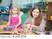 Купить «Счастливая мама и недовольный ребенок с подарками», фото № 4200876, снято 24 декабря 2012 г. (c) Кекяляйнен Андрей / Фотобанк Лори