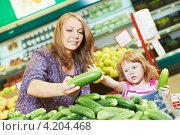 Купить «Женщина с дочерью выбирают огурцы в магазине», фото № 4204468, снято 18 июня 2012 г. (c) Дмитрий Калиновский / Фотобанк Лори