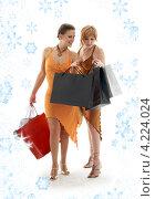 Купить «Две счастливые покупательницы с покупками на фоне со снежинками», фото № 4224024, снято 19 августа 2006 г. (c) Syda Productions / Фотобанк Лори