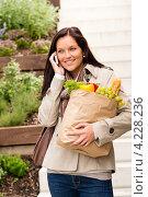 Улыбающаяся девушка с продуктами разговаривает по сотовому телефону. Стоковое фото, фотограф CandyBox Images / Фотобанк Лори