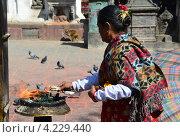 Непальская женщина совершает буддистский ритуал в храмовом комплексе Своятбутнатх (2012 год). Стоковое фото, фотограф Овчинникова Ирина / Фотобанк Лори