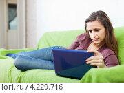 Купить «Девушка с ноутбуком лежит на диване дома», фото № 4229716, снято 17 ноября 2012 г. (c) Яков Филимонов / Фотобанк Лори