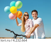 Счастливая молодая пара на велосипеде стоит на фоне голубого неба. Молодой человек и девушка держат разноцветные надувные шарики в руках. Стоковое фото, фотограф Дарья Петренко / Фотобанк Лори