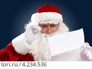 Купить «Дед Мороз с большой белой бородой в очках читает новогоднее письмо на черном фоне», фото № 4234536, снято 28 сентября 2012 г. (c) Sergey Nivens / Фотобанк Лори