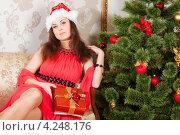 Купить «Молодая брюнетка с новогодним подарком в руках», фото № 4248176, снято 8 января 2013 г. (c) Сергей Дубров / Фотобанк Лори