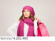 Купить «Девушка в вязаной розовой шапке и шарфе с покупками в пакетах в руках», фото № 4262480, снято 10 октября 2010 г. (c) Syda Productions / Фотобанк Лори