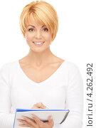 Купить «Привлекательная молодая женщина со стрижкой пишет что-то в блокноте», фото № 4262492, снято 26 сентября 2010 г. (c) Syda Productions / Фотобанк Лори