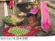 Пожилая раджастанская женщина продает фрукты на рынке во время ежегодной верблюжьей ярмарки в Пушкаре, Раджтастан, Индия (2012 год). Редакционное фото, фотограф крижевская юлия валерьевна / Фотобанк Лори