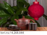 Керамический китайский чайник и чашки на бамбуковой салфетке. Стоковое фото, фотограф Сергей Лукин / Фотобанк Лори