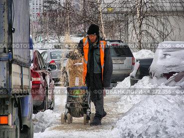 Купить «Дворник - гастарбайтер посыпает тротуар реагентами, Новокосинская улица, район Новокосино, Москва», эксклюзивное фото № 4272356, снято 5 февраля 2013 г. (c) lana1501 / Фотобанк Лори