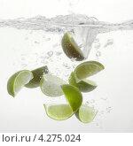 Купить «Дольки лайма, падающие в воду и пузыри воздуха», фото № 4275024, снято 19 января 2019 г. (c) Food And Drink Photos / Фотобанк Лори