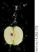Половина яблока в брызгах на черном фоне. Стоковое фото, фотограф Рыбаков Сергей / Фотобанк Лори