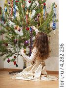 Купить «Девочка в праздничном платье наряжает новогоднюю елку», фото № 4282236, снято 9 января 2013 г. (c) Юлия Машкова / Фотобанк Лори