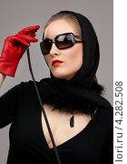 Купить «Девушка в платке, солнечных очках и красных перчатках с хлыстом в руке», фото № 4282508, снято 1 марта 2008 г. (c) Syda Productions / Фотобанк Лори