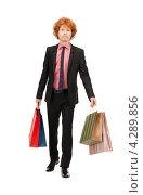 Купить «Рыжий молодой человек в черном костюме с разноцветными пакетами после шоппинга», фото № 4289856, снято 26 февраля 2011 г. (c) Syda Productions / Фотобанк Лори
