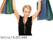 Купить «Довольная покупательница улыбается, стоя с пакетами в руках», фото № 4291844, снято 12 февраля 2011 г. (c) Syda Productions / Фотобанк Лори
