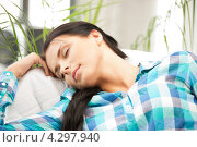 Купить «Очаровательная девушка в клетчатой рубашке отдыхает на диване дома», фото № 4297940, снято 16 июня 2019 г. (c) Syda Productions / Фотобанк Лори