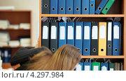 Купить «Деловая женщина ищет нужную папку с документами на полках шкафа», видеоролик № 4297984, снято 17 февраля 2013 г. (c) Кекяляйнен Андрей / Фотобанк Лори