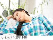 Купить «Очаровательная девушка в клетчатой рубашке отдыхает на диване дома», фото № 4298148, снято 17 июля 2019 г. (c) Syda Productions / Фотобанк Лори