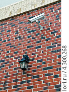 Уличный фонарь с энергосберегающей лампой и камера видеонаблюдения на стене дома, отделанной облицовочной плиткой. Стоковое фото, фотограф Сергей Трофименко / Фотобанк Лори