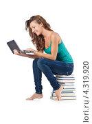 Купить «Улыбающаяся студентка сидит на стопке книг с ноутбуком», фото № 4319920, снято 22 августа 2012 г. (c) Elnur / Фотобанк Лори