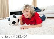 Купить «Мальчик болеет парад телевизором за футбольную команду, лежа рядом с футбольным мячом», фото № 4322404, снято 12 ноября 2019 г. (c) Wavebreak Media / Фотобанк Лори