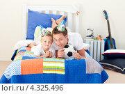 Купить «Отец с сыном болеют за футбол по телевизору на кровати», фото № 4325496, снято 18 октября 2009 г. (c) Wavebreak Media / Фотобанк Лори