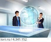Купить «Двое привлекательных бизнесменов - мужчина и женщина в офисе возле трехмерного виртуального глобуса», фото № 4341152, снято 12 декабря 2012 г. (c) Sergey Nivens / Фотобанк Лори