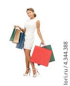 Красивая молодая женщина с многочисленными покупками в пакетах на белом фоне. Стоковое фото, фотограф Syda Productions / Фотобанк Лори