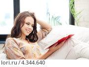 Купить «Счастливая девушка с увлечением читает книгу, сидя на диване», фото № 4344640, снято 16 июля 2011 г. (c) Syda Productions / Фотобанк Лори